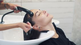 Close up hand of hairdresser washes hair to woman in beauty salon, slow motion stock video footage
