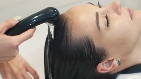 Close up hand of hairdresser washes hair to woman in sink, slow motion stock footage