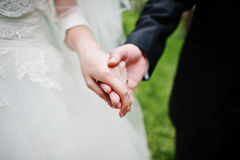 Close up hand in hand of wedding couple. Stock Photos