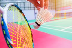 Close up hand hold serve badminton shuttlecock badminton court background. Close up hand hold serve badminton shuttlecock with blur badminton court background stock image