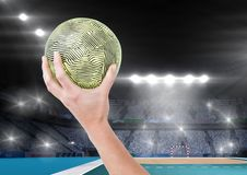 Close-up of hand holding ball and stadium in background Stock Photos