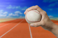 Hand holding a baseball on red running track with blue sky Royalty Free Stock Photo