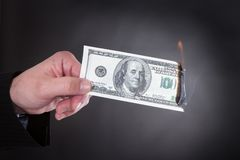 Close-up Of Hand Holding Burning Banknote Royalty Free Stock Photography