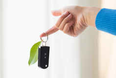 Close up of hand holding car key with green leaf Stock Photo