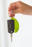 Close up of hand holding car key with green leaf Royalty Free Stock Photography