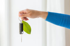 Close up of hand holding car key with green leaf Royalty Free Stock Image