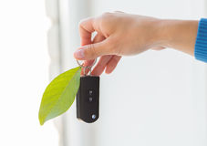 Close up of hand holding car key with green leaf Royalty Free Stock Photo