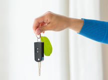 Close up of hand holding car key with green leaf Stock Image