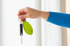 Close up of hand holding car key with green leaf Stock Photography