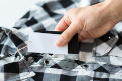 Close up of hand holding checkered shirt price tag Stock Photos