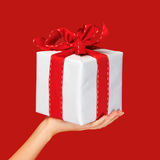 Close up hand holding christmas gift box over red Royalty Free Stock Photos