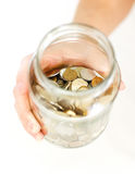 Close up hand holding coins in glass jar on white table. Isolate Stock Image