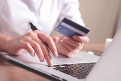 Close up hand holding credit card and using laptop. stock image