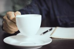 close up hand holding cup of coffee on working table stock photography