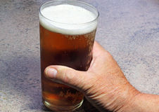 Close up of a hand holding drink in a pint glass. Stock Photography