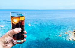 Hand holding drinking glass with ice-cooled cola against blue sky and sea. Close-up of hand holding drinking glass with ice-cooled cola against blue sky and sea stock images