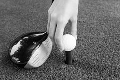 Close-up Hand holding golf ball and a golf wood on a driving ran Royalty Free Stock Photos