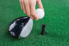 Close-up Hand holding golf ball and a golf wood on a driving ran Stock Images