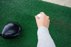 Close-up Hand holding golf ball and a golf wood on a driving ran Stock Image