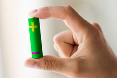 Close up of hand holding green alkaline battery Stock Images