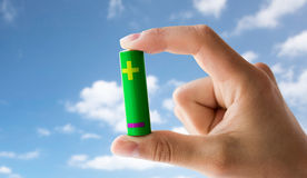 Close up of hand holding green alkaline battery Royalty Free Stock Photos