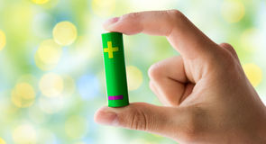 Close up of hand holding green alkaline battery Royalty Free Stock Photography