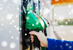 Close up of hand holding hose at gas station Stock Images