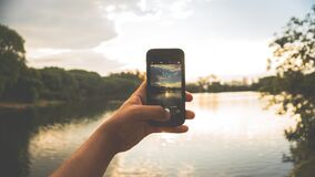 Close-up of Hand Holding Mobile Phone Against Lake Royalty Free Stock Images