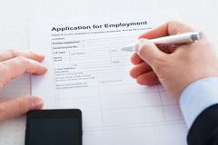 Close-up Of Hand Holding Pen Over Employment Application. With Mobile Phone Stock Image
