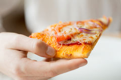 Close up of hand holding pizza slice. People, fast food, italian kitchen and eating concept - close up of hand holding pizza slice stock photos