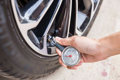 Close-Up Of Hand holding pressure gauge. For car tyre pressure measurement Stock Photography