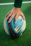 Close up of hand holding rugby ball. On field stock image