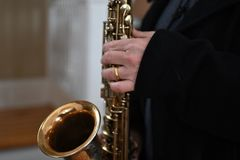 Senior man play saxophone in the party. Close up hand holding the saxophone Stock Images