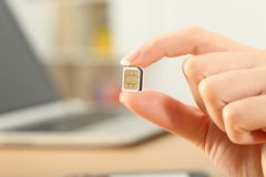 Close up of a hand holding a sim card. At home Stock Images
