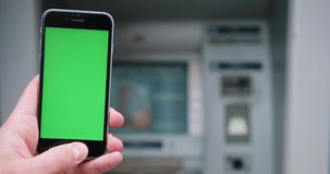 Close up of hand holding a smartphone with green screen display on the street. Chroma key. Vertical. Shot on RED Cinema. Camera in 4K stock video