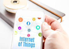 Close up hand holding smartphone with Internet of things word an Stock Image