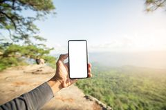 Hand  holding smartphone on nature backgound Royalty Free Stock Photo