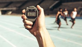 Man keeping time at a running race using stop watch. Close up of a hand holding a stop watch for time keeping at a running race. Athletes running a race while royalty free stock image