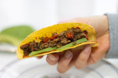 Close-up of hand holding a taco. With vegetarian filling of corn, red pepper, beans, soy meat, avocado, dip on blurred light background Royalty Free Stock Photos