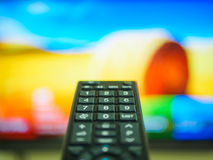 Close up Hand holding TV remote control. With a television in the background Stock Photos