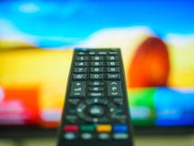 Close up Hand holding TV remote control. With a television in the background Royalty Free Stock Photography