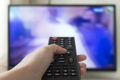 Close up Hand holding TV remote control with a television in the background. stock images