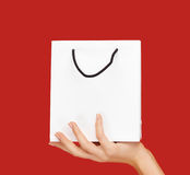 Close up of hand holding white bag over red Stock Photos