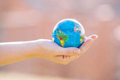 Close up of a hand holding the world. Close up of a hand holding the world isolated outside royalty free stock photo