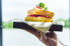 Close up hand holds Belgian waffles on tray Royalty Free Stock Photography