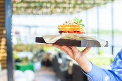 Close up hand holds Belgian waffles on tray Stock Photo