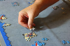 Close up of a hand inserting a piece of jigsaw puzzle. Stock Images
