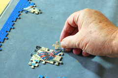 Close up of a hand inserting a piece of jigsaw puzzle. Royalty Free Stock Photography