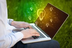 Close up of hand with laptop and  idea bulb Stock Images