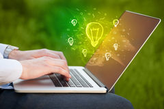 Close up of hand with laptop and  idea bulb Stock Photos